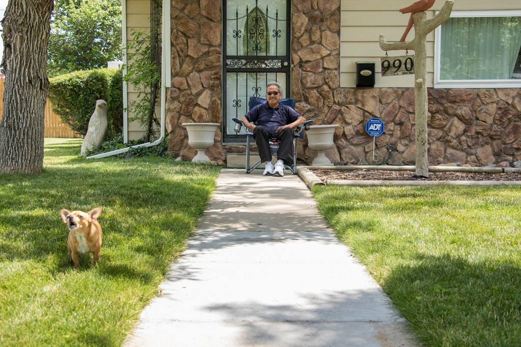 Ray Arguellos, and his dog Zoe, hangs out in his Villa Park yard a block from Federal Boulevard, July 20, 2018. (Kevin J. Beaty/Denverite)