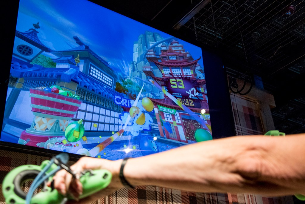 """""""Fruit Ninja"""" on the screen inside the new virtual reality parlor open at Punch Bowl Social Broadway, July 18, 2018. (Kevin J. Beaty/Denverite)"""