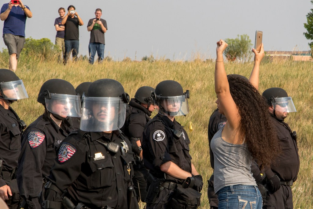 Hanna Khavafipout rages against police as they surround immigration activists who blockaded the local headquarters for U.S. Immigrations and Customs Enforcement in Centennial, Aug. 2, 2018. (Kevin J. Beaty/Denverite)