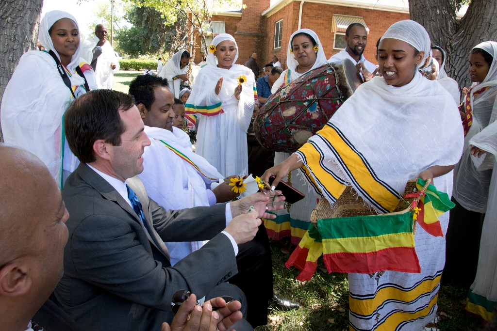 Elene Abera collects alms, here from U.S. House candidate Jason Crow, after an Ethiopian New Year service at St. Mary Ethiopan Orthodox Church. Aurora, Sept. 9, 2018. (Kevin J. Beaty/Denverite)