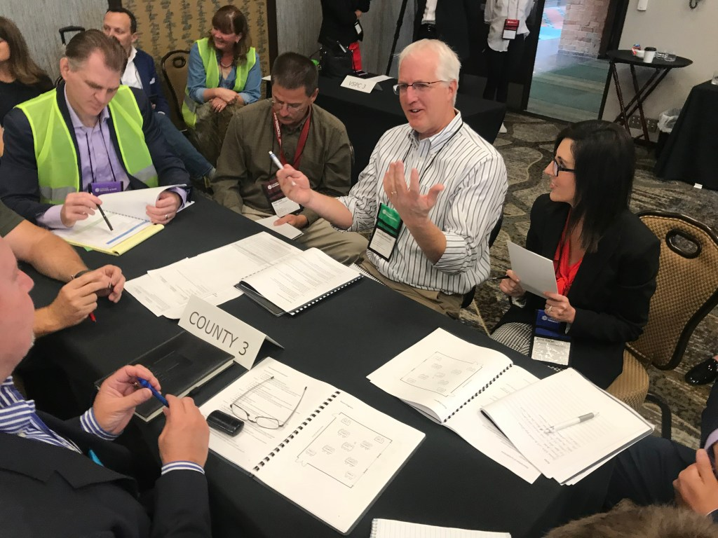 Jefferson County Elections Director Gary VanDeStouwe (center) leads a discussion in during an election preparedness exercise on Thursday, Sept. 5, at the Hilton Denver Inverness in Englewood. (Esteban L. Hernandez/Denverite)