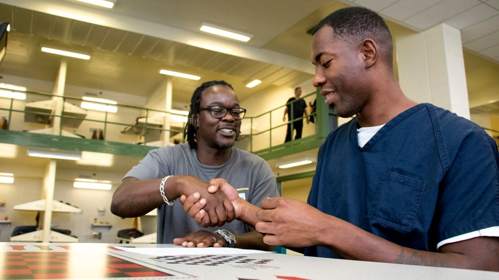 Colorado Criminal Justice Reform Coalition deputy director Juston Cooper shakes hands with Jamayl Norris after helping him register to vote inside Denver's downtown detention center. Oct. 11, 2018. (Kevin J. Beaty/Denverite)