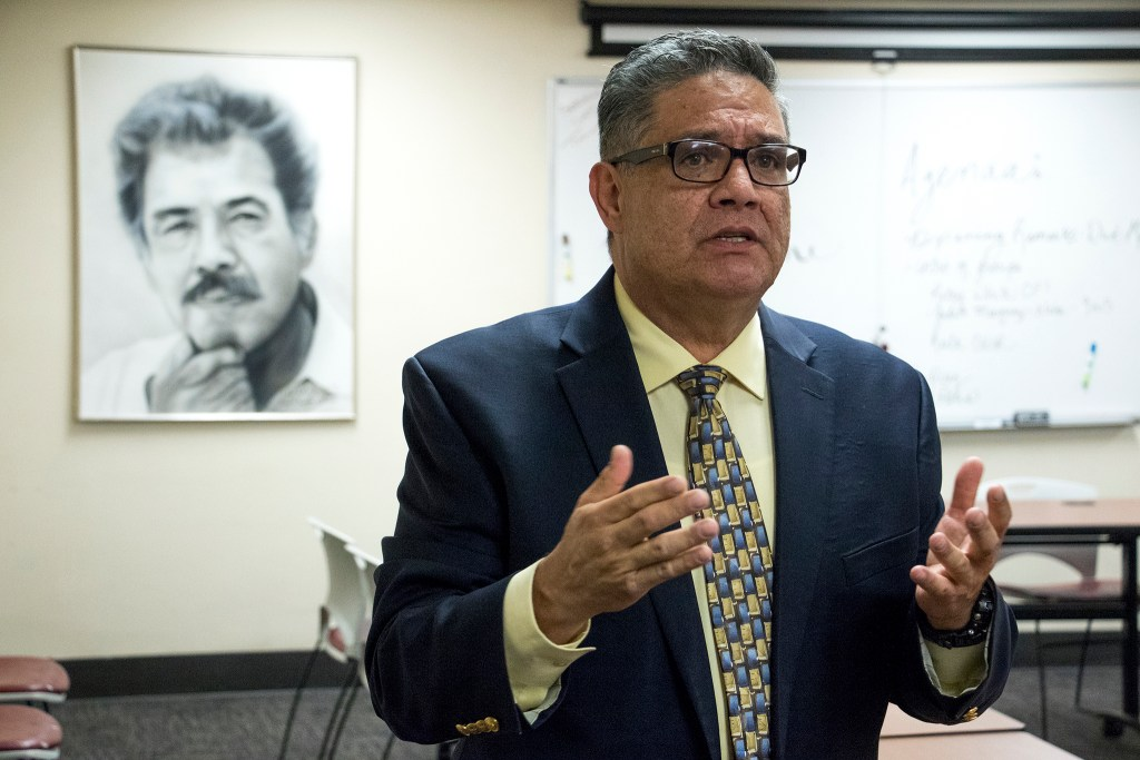 Servicios de la Raza executive director Rudy Gonzales welcomes a delegation of Colorado Democrat candidates. That's a picture of his father, Corky Gonzales, behind him. Oct. 30, 2018. (Kevin J. Beaty/Denverite)