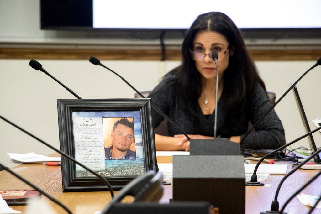 Joelle Fairchild speaks to Denver City Council about safe injection sites with a photo of her son, Tony, in front of her, Nov. 7, 2018. (Kevin J. Beaty/Denverite)