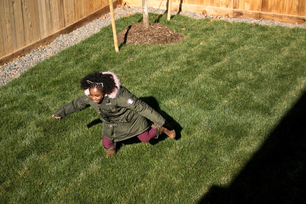 Amaya Jackson sprints around her family's new backyard in Commerce City, Nov. 9, 2018. (Kevin J. Beaty/Denverite)