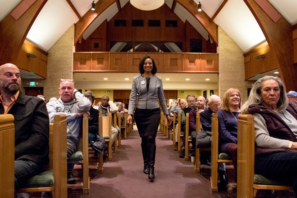 Lisa Calderón walks on stage during a public forum for Denver mayoral candidates at Messiah Community Church in South Park Hill, Nov. 13, 2018. (Kevin J. Beaty/Denverite)