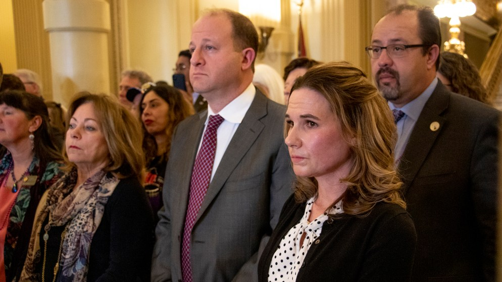 Erin Martinez stands alongside lawmakers and Governor Jared Polis during a press conference on a new bill changing oil and gas regulations, Feb. 28, 2019. (Kevin J. Beaty/Denverite)