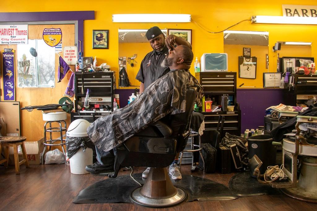 "Ed ""Tank"" Thomas cuts Derrick Webster's hair at Tank's World Class Barber shop on East Colfax Avenue, March 11, 2019. (Kevin J. Beaty/Denverite)"