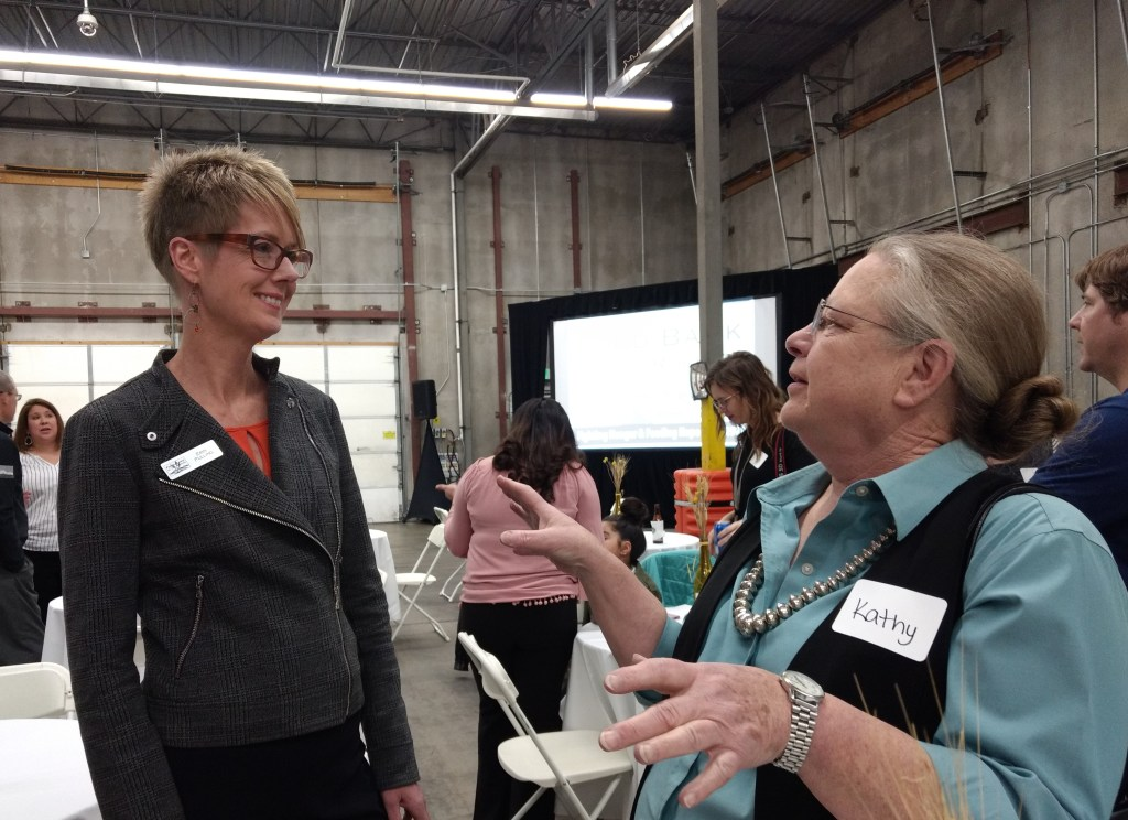 Kathy Groth, right, who founded the organization that would grow into the Food Bank of the Rockies, chats with food bank CEO Erin Pulling at the nonprofit's 40th anniversary celebration on Feb. 28. (Donna Bryson/Denverite)