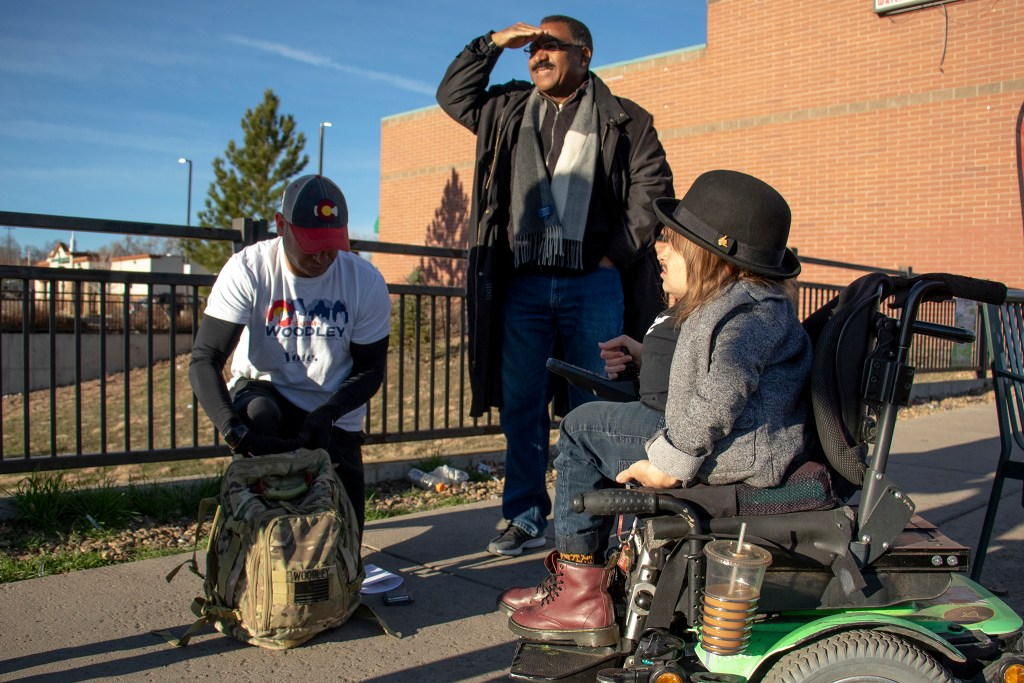 District 9 candidate Jonathan Woodley (left to right) and mayoral candidates Pendfield Tate and Kayln Rose Heffernan wait at a bus stop on Alameda. Denver Streets Partnership's Amazing Denver Mobility Race, April 4, 2019. (Kevin J. Beaty/Denverite)
