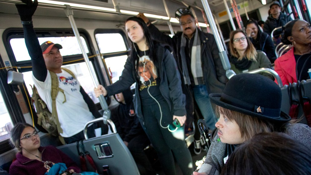 District 9 candidate Jonathan Woodley (left to right) and mayoral candidates Pendfield Tate and Kayln Rose Heffernan ride an eastbound #3 bus. Denver Streets Partnership's Amazing Denver Mobility Race, April 4, 2019. (Kevin J. Beaty/Denverite)