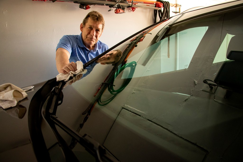 George Mayl,  president of the Inter-Neighborhood Cooperation, waxes his car in his Belcaro garage. April 19, 2019. (Kevin J. Beaty/Denverite)