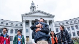 Kevin Matthews hugs David Champion at a pro-Initiative 301 press conference, May 9, 2019. (Kevin J. Beaty/Denverite)