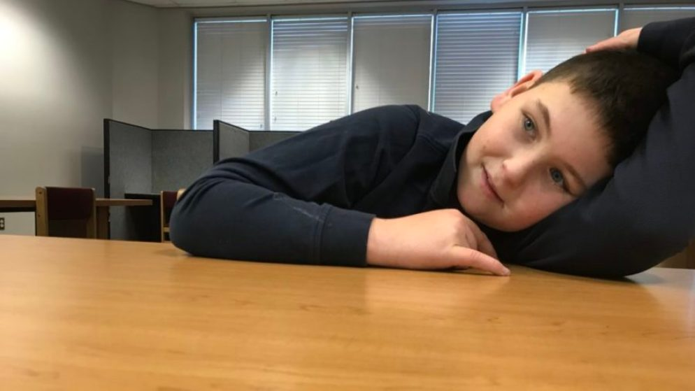 Jake DiProfio rests his head on a table at the local library during a tutoring session. (Melanie Asmar/Chalkbeat)
