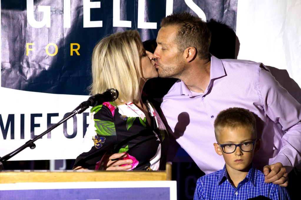 After conceding defeat in the Denver mayor's runoff election to incumbent Michael Hancock, Jamie Giellis kisses her husband Chris as her 8-year old stepson Jackson waits on the podium at Ophelia's in downtown Denver Tuesday June 4 2019. (Hart Van Denburg/CPR News)