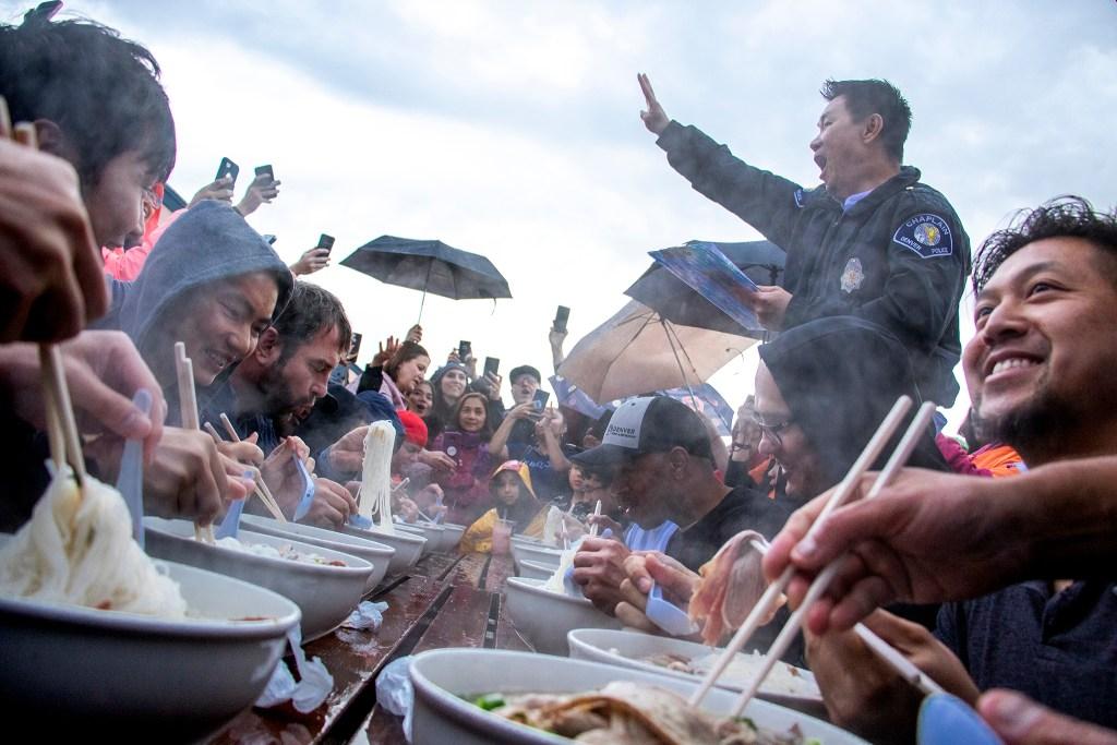 Father Joseph Dang initiates a pho eating context during the Little Saigon Night Market. Federal Boulevard, June 21, 2019. (Kevin J. Beaty/Denverite)