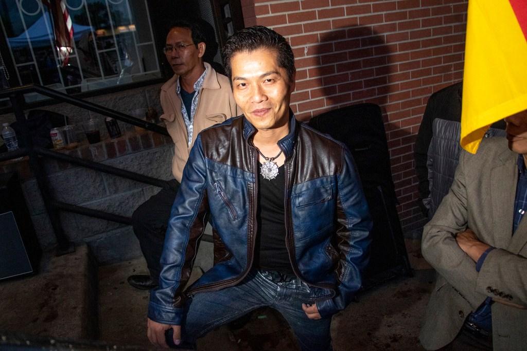 Trieu Hoang listens as Los Mocochetes plays the Little Saigon Night Market. Federal Boulevard, June 21, 2019. (Kevin J. Beaty/Denverite)