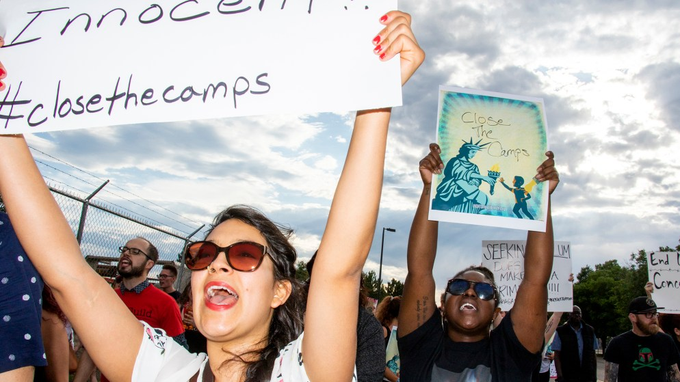 Angeliky Santos (left) marches with protesters to Aurora's private immigration detention facility, denouncing ICE raids and jails like it across the country, June 14, 2019. (Kevin J. Beaty/Denverite)