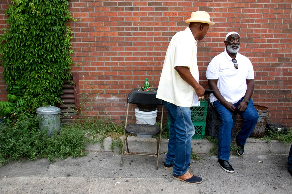 Irv Lyord and Flynn Dickerson joke around behind the restaurant. Welton Street Cafe celebrates 20 years in one location. Five Points, July 30, 2019. (Kevin J. Beaty/Denverite)