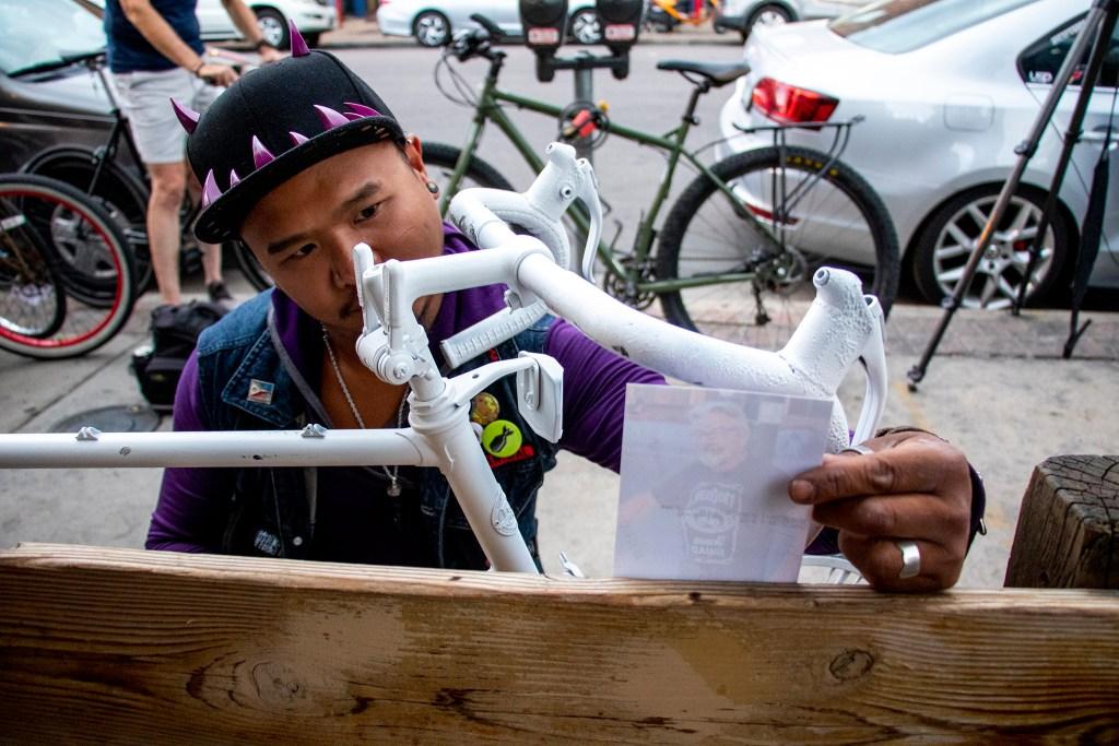 Choko Malic looks at a photo of Scott Hendrickson, placed on his ghost bike, before the Denver Cruiser Ride, July 31, 2019. (Kevin J. Beaty/Denverite)