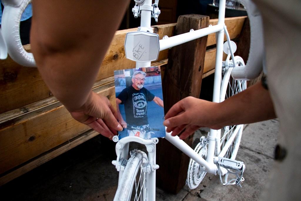 Jackie Olszewski places a photo of Scott Hendrickson on his ghost bike before the Denver Cruiser Ride, July 31, 2019. (Kevin J. Beaty/Denverite)