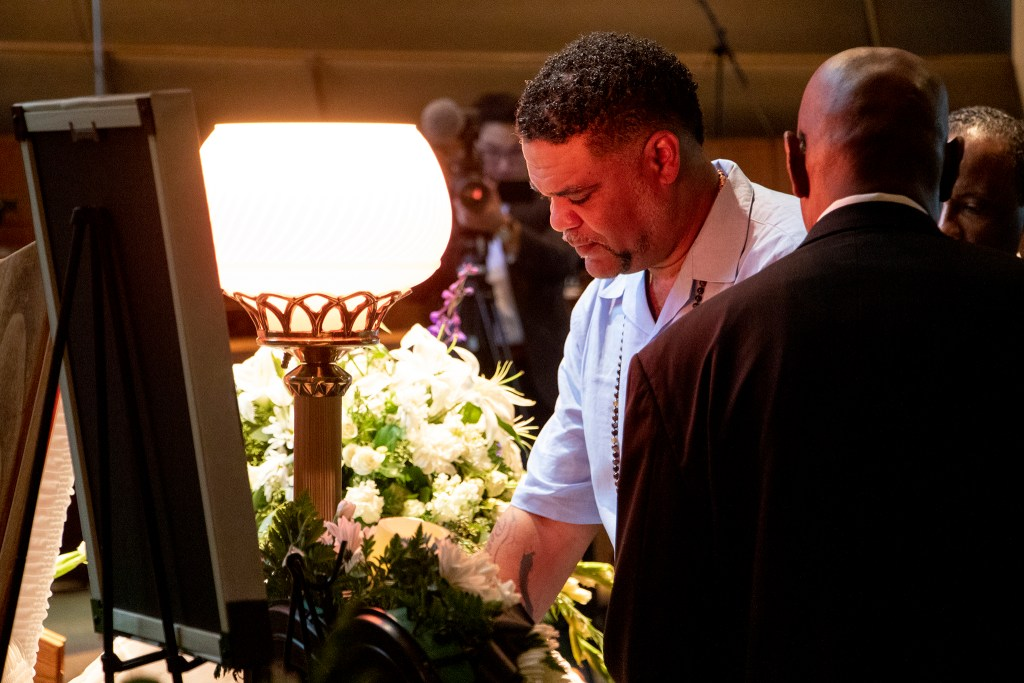 "Hasira ""Soul"" Ashemu peers into the casket of his father, Colorado Black Panther Party founder Lauren Watson, during his funeral, Aug. 21, 2019. (Kevin J. Beaty/Denverite)"
