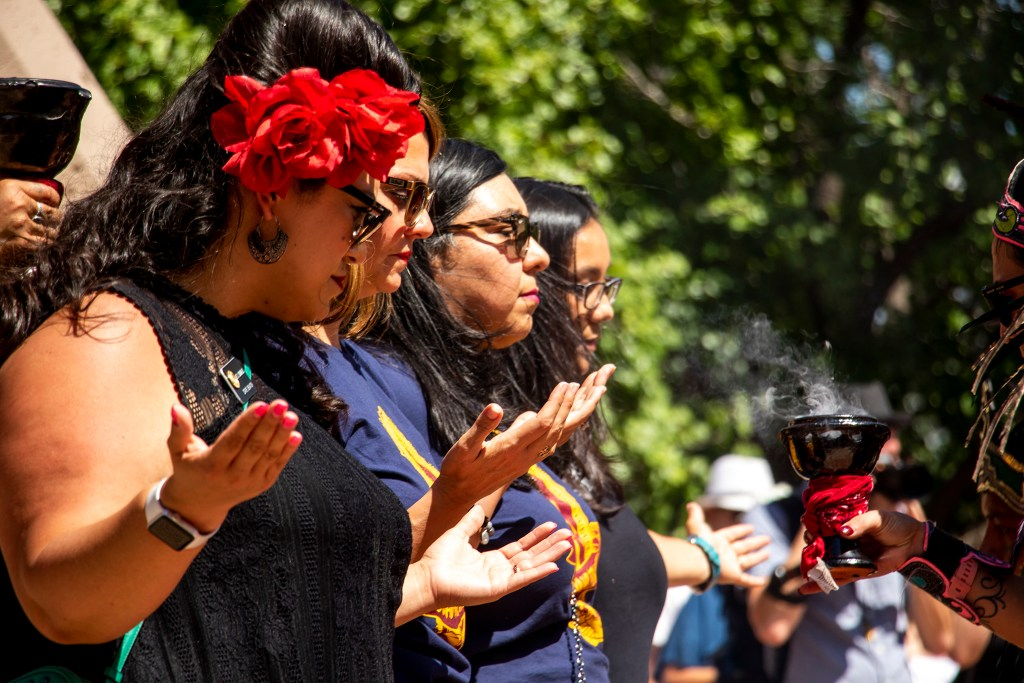 Stare Sen. Julie Gonzales (left to right), City Councilwomen Amanda Sandoval and Jamie Torres and State House Rep. Serena Gonzales-Gutierrez are blessed with smoke at La Raza (or Columbus) Park before a cruise down Federal Boulevard. Aug. 25, 2019. (Kevin J. Beaty/Denverite)