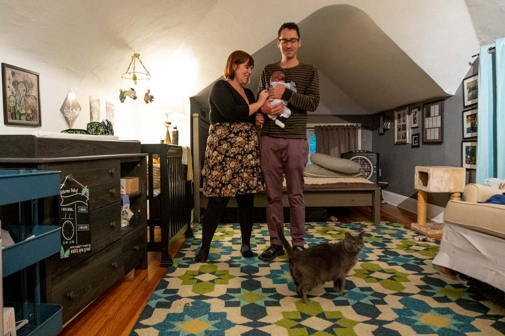 Sarah Wells, Stephen Polk and their son, Charlie, inside their bedroom at the co-op home at 901 N. Clarkson St. Oct. 1, 2019. (Kevin J. Beaty/Denverite)