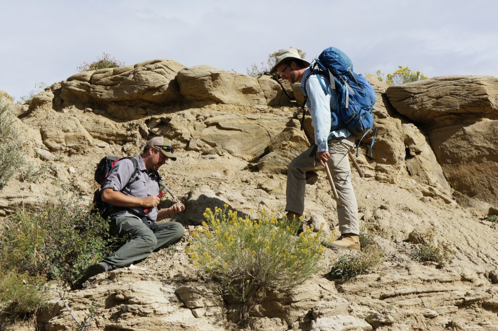 Dr. Ian Miller (left), curator of paleobiology at the Denver Museum of Nature & Science, and Dr. Tyler Lyson curator of paleontology at the Denver Museum of Nature & Science) look for fossil concretions at the Corral Bluffs site. (Courtesy: HHMI Tangled Bank Studios)