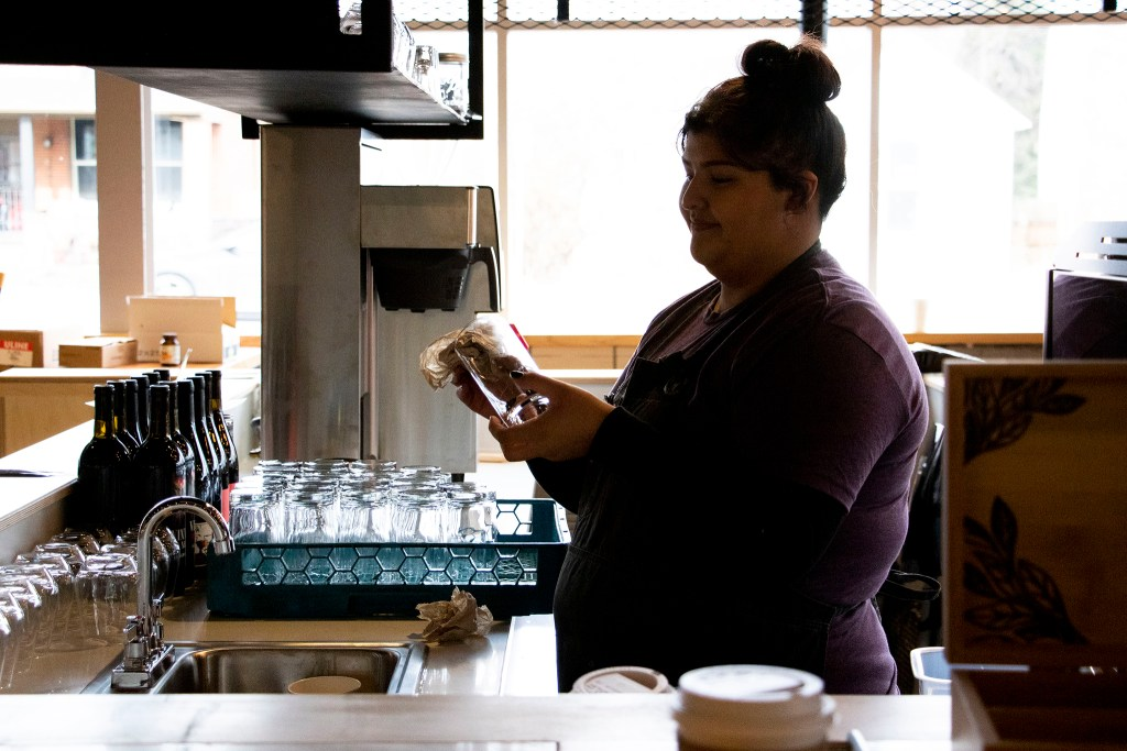 Barista Kendra Ulloa cleans a glass behind the bar at Leevers Locavore Northside, Nov. 20, 2019. (Kevin J. Beaty/Denverite)