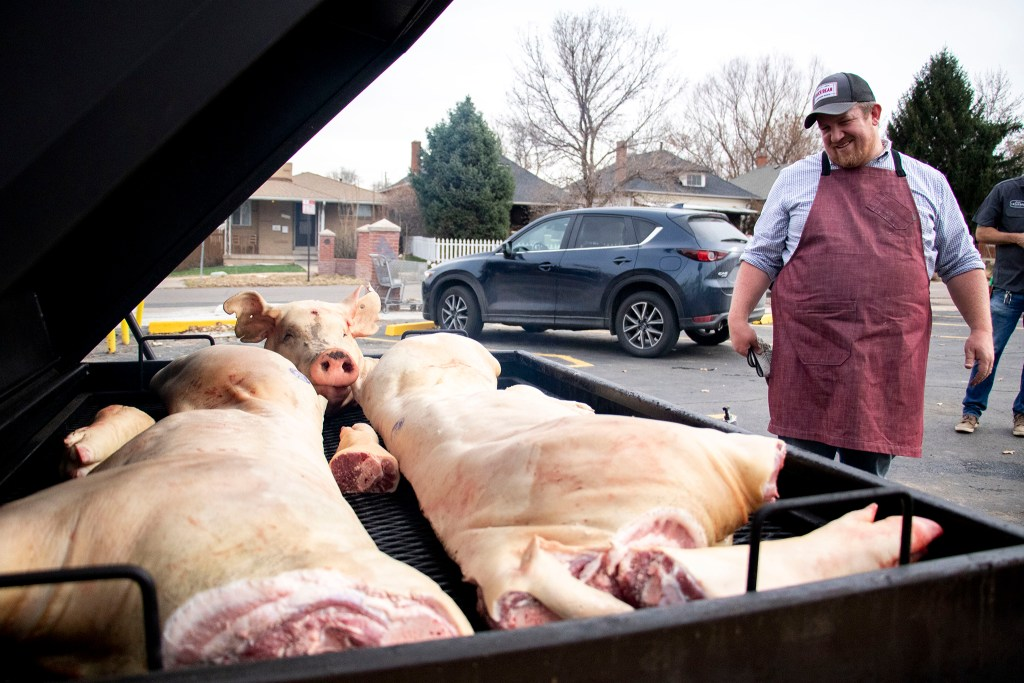 River Bear American Meats chef Ben Warren cooks a pig for Leevers Locavore Northside's grand opening on 38th Avenue. Nov. 20, 2019. (Kevin J. Beaty/Denverite)