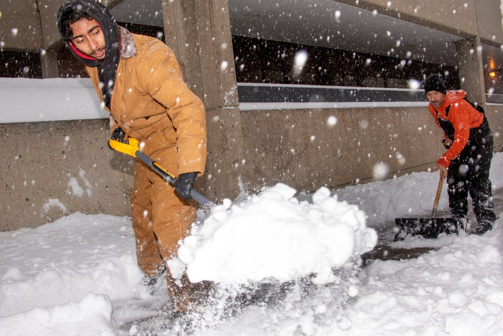 Jovony (left) and Hondo Padilla shovel snow on Lincoln Street, Nov. 26, 2019. (Kevin J. Beaty/Denverite)