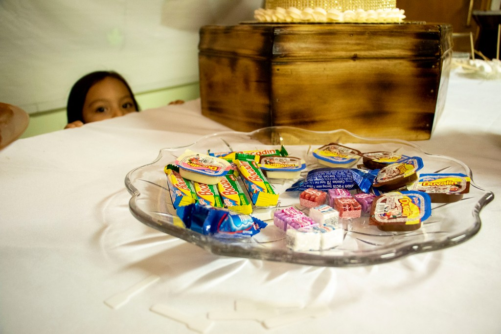Kim Ramos sister, Melanie, eyes a plate of candy during Ramos' quinceañera. Ministerio Hispano Presbyterian Church, Dec 14, 2019. (Kevin J. Beaty/Denverite)