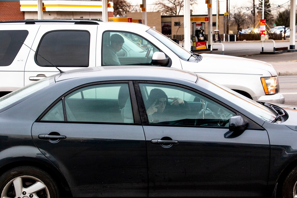 A driver hails a photographer at the corner of Federal Boulevard and Florida Avenue, Jan. 16, 2020. (Kevin J. Beaty/Denverite)