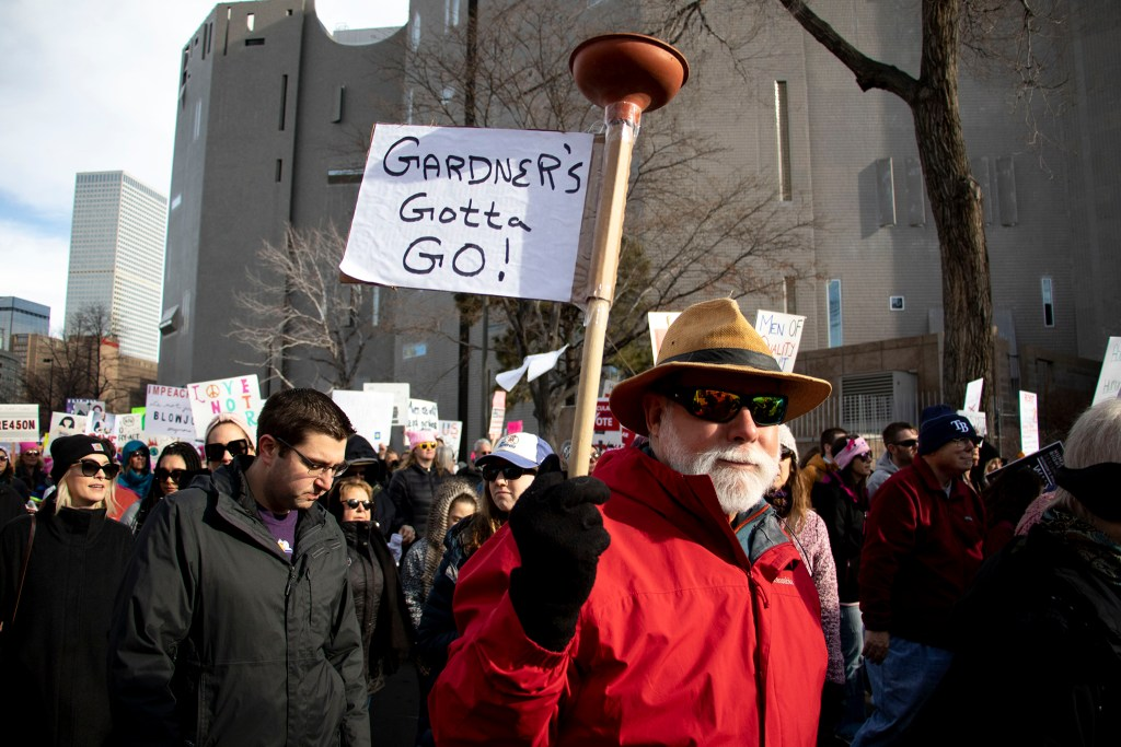 Karl Dise holds up a plunger with a call to action on it. Denver Womxn's March, Jan. 18, 2020. (Kevin J. Beaty/Denverite)