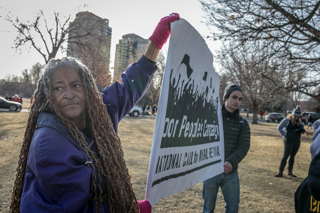 Michelle Diane of the Colorado Poor People's Campaign holds a sign. (Hart Van Denberg/CPR News)