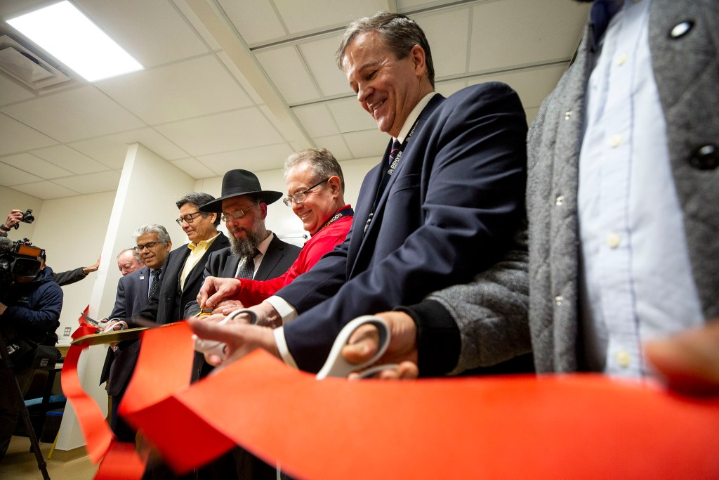 Faith leaders and officials cut the ribbon on the newly installed Lodox full-body imaging system at Denver's Office of the Medical Examiner. Feb. 5, 2020. (Kevin J. Beaty/Denverite)