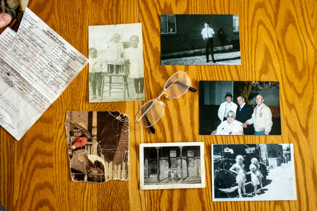 An array of old photos of Joseph Martinez's family, laid out on his diningroom table. Feb. 12, 2020. (Kevin J. Beaty/Denverite)