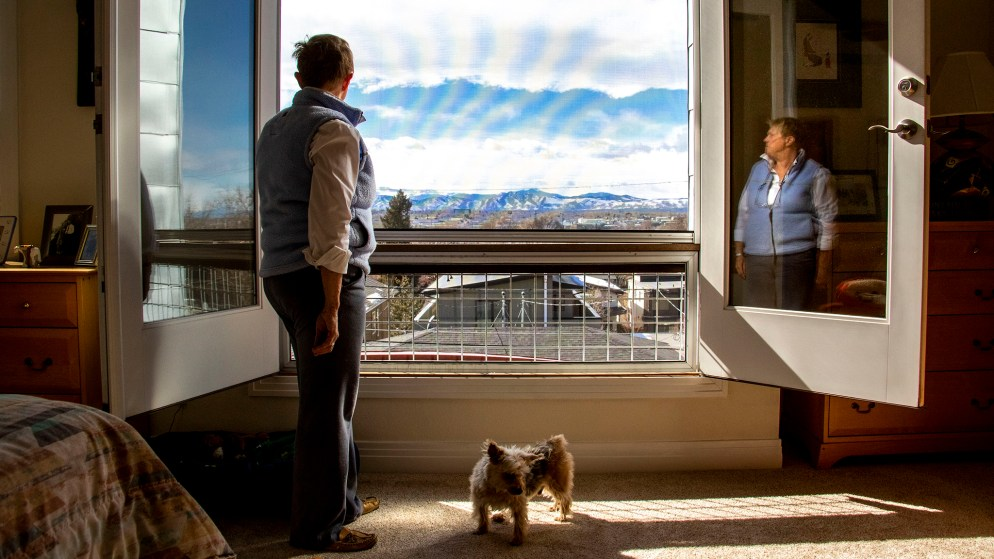 Sandy Pierce looks out onto the view from her home in Denver's Rosedale neighborhood as her dog, Buckaroo, stands by. Feb. 27. 2020.  (Kevin J. Beaty/Denverite)