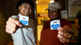 Elizabeth Ngirailab and Bria Daniel pose for a portrait with their stickers on Super Tuesday at the Hiawatha Davis recreation center in Northeast Park Hill, March 3, 2020. (Kevin J. Beaty/Denverite)