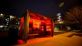 A solar-powered bus shelter is illuminated in  candy-apple red. West Colfax Avenue, March 12, 2020. (Kevin J. Beaty/Denverite)