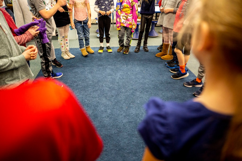 Second graders stand in a circle for a game in Kari Notton's class at Carson Elementary, March 13, 2020. (Kevin J. Beaty/Denverite)
