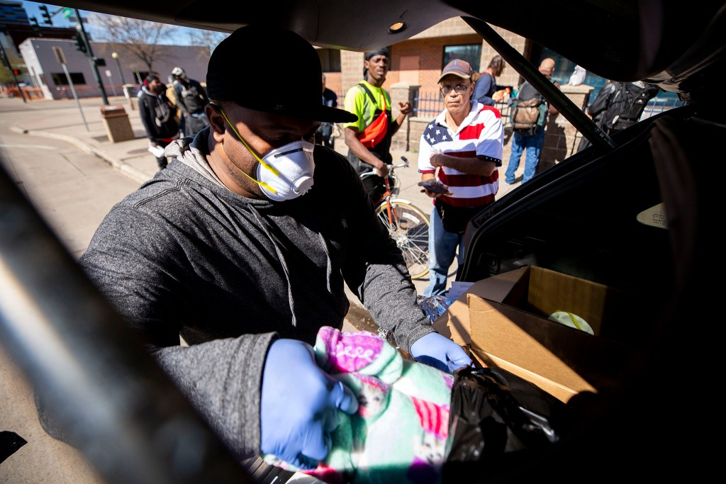 Mario McDonald distributes blankets and quesadillas on the street by Denver Rescue Mission and Samaritan House. March 24, 2020. (Kevin J. Beaty/Denverite)