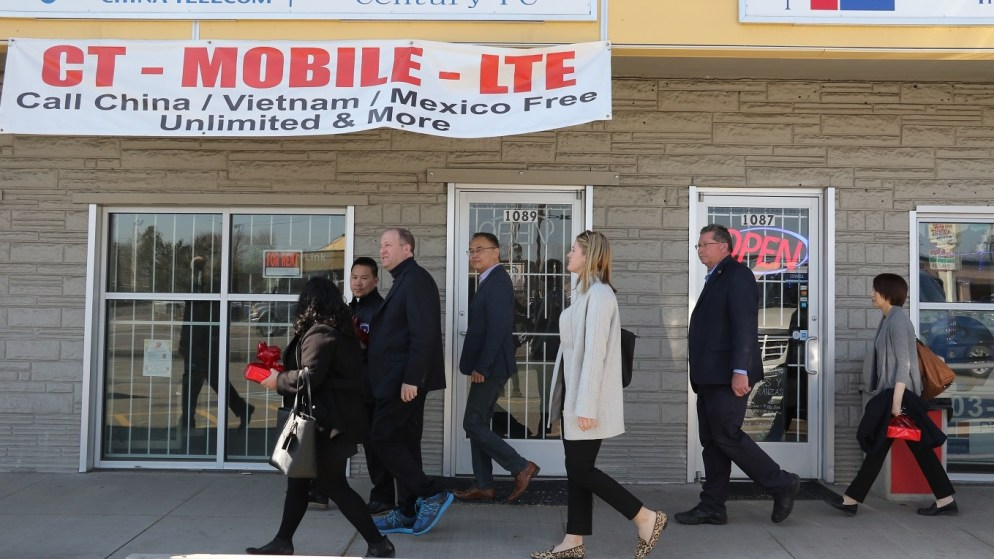 Gov. Jared Polis (center, in the blue shoes) walks down a shopping center during a tour of Asian businesses on Monday, March 2, in Denver. (Esteban L. Hernandez/Denverite)