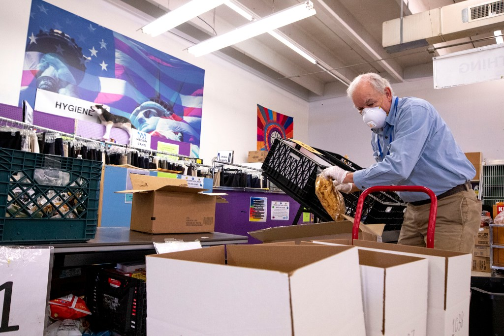 Griff McClure packs food into boxes at the Mental Health Center of Denver. April 3, 2020. (Kevin J. Beaty/Denverite)