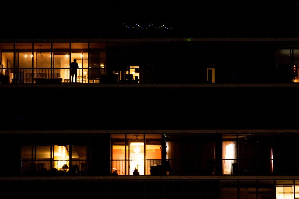 An apartment dweller peers down upon Cheesman Park. April 7, 2020. (Kevin J. Beaty/Denverite)