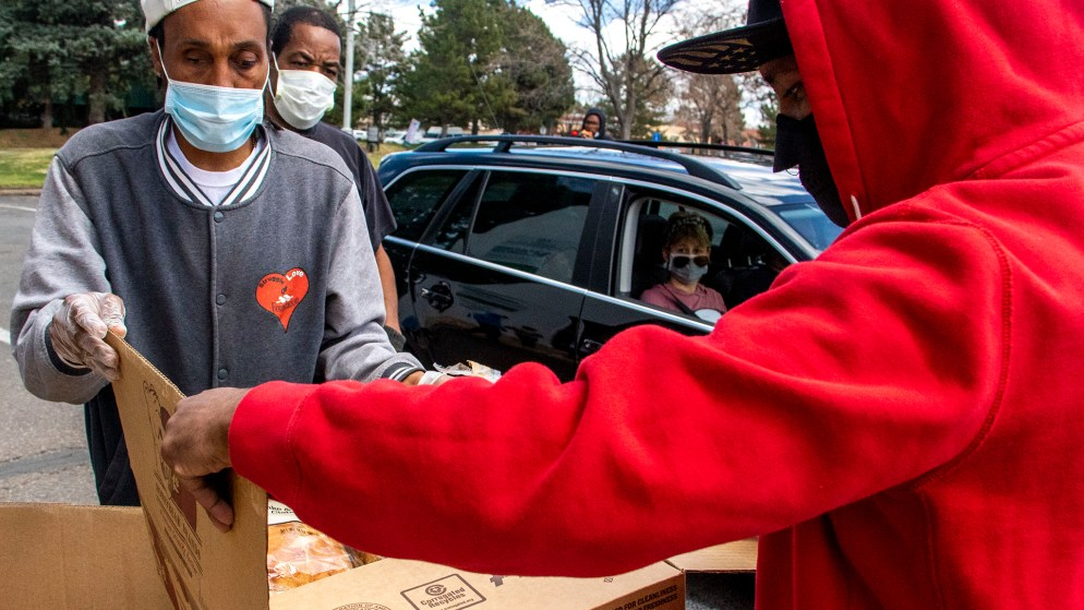 Joel Hodge (left) and Tyrice Catano Sr. unpack boxes of food at the Struggle of Love Foundation's Montbello food pantry. April 24, 2020. (Kevin J. Beaty/Denverite)