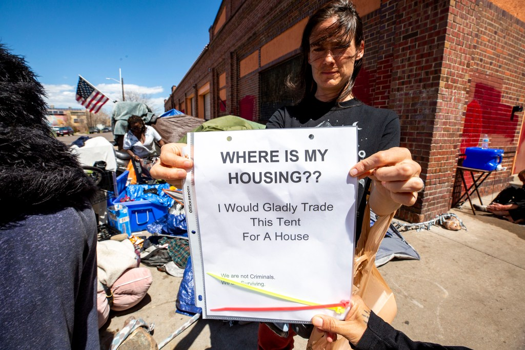 Terese Howard of Denver Homeless Out Loud holds up a sign she's distributing to people camping on California Street. April 28, 2020. (Kevin J. Beaty/Denverite)