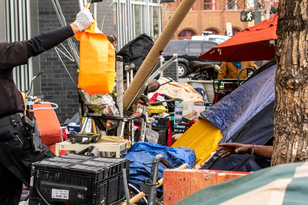 Denver Police Officer Toby Wilson hands a trash bag to a woman living in a tent during a multi-agency cleanup of homeless encampments near the intersection of 22nd and Champa Streets in Five Points. April 30, 2020. (Kevin J. Beaty/Denverite)