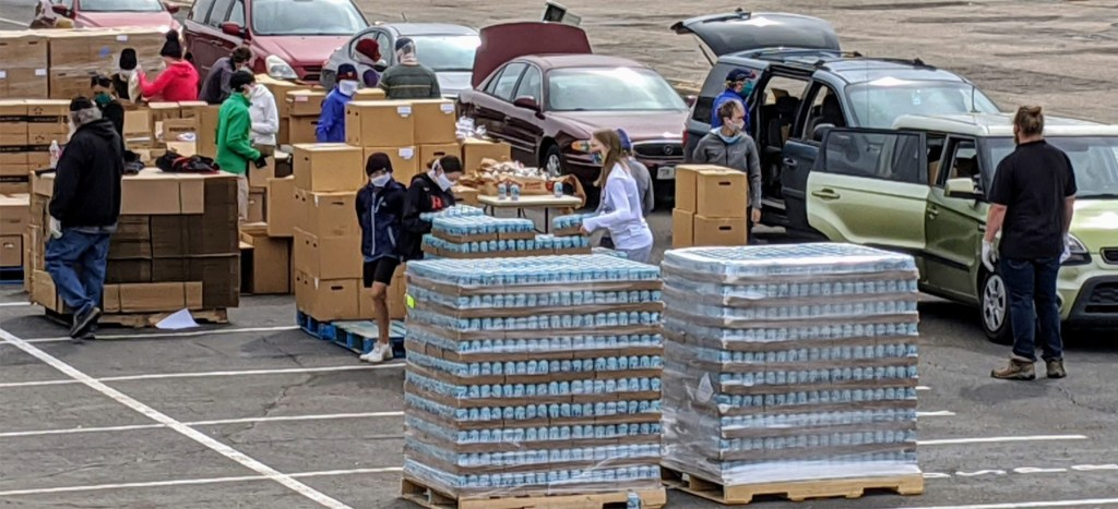A Food Bank of the Rockies senior box and family food distribution takes place in the parking lot of a school, Academy 360 in Montbello, on April 18, 2020. The school's lot allowed more space than the food bank's own warehouse nearby for a drive-through distribution, a model that reduces the person-to-person contact that can spread the coronavirus. (Donna Bryson/Denverite)